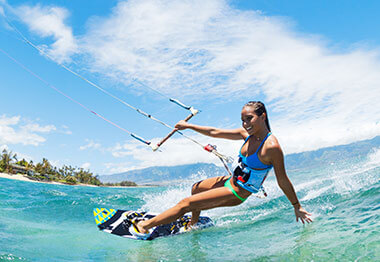 Young Dominican woman riding the surf by kite