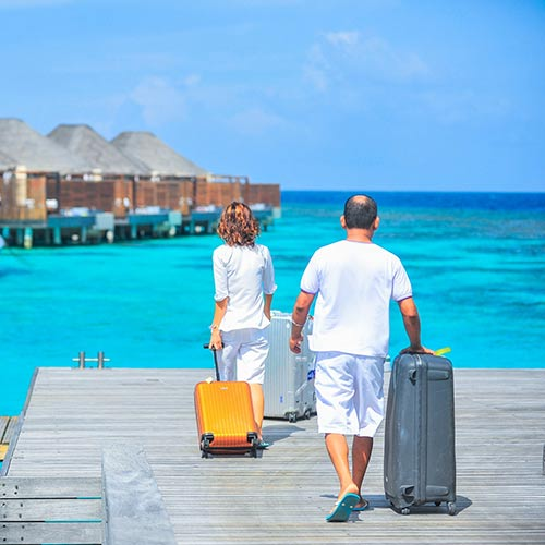 Couple with luggage walking dock to ocean