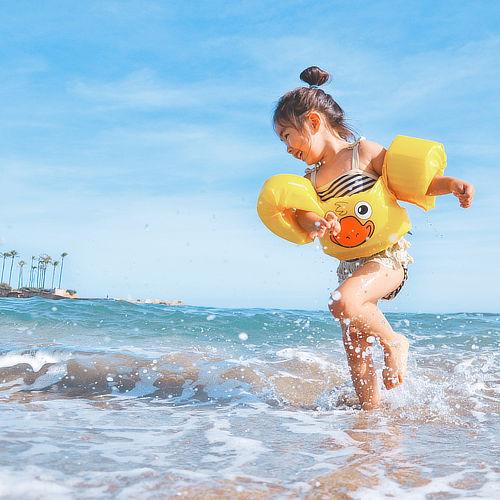 Little girl wearing water wings plays in waves along beach