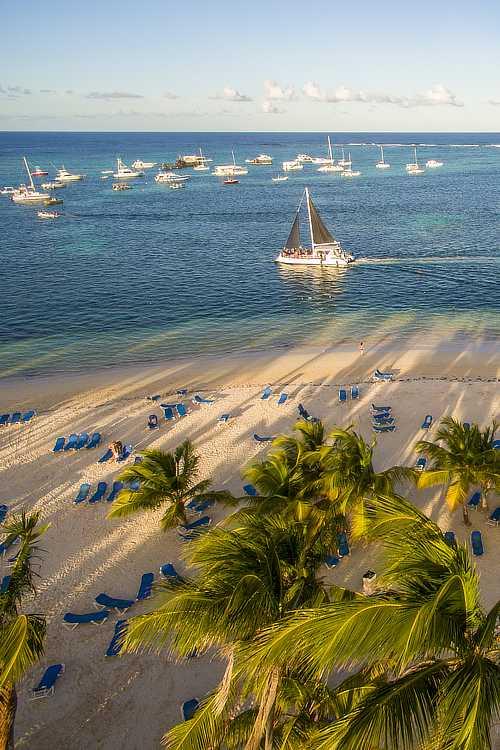 Sail boats pass the beach at Cap Cana