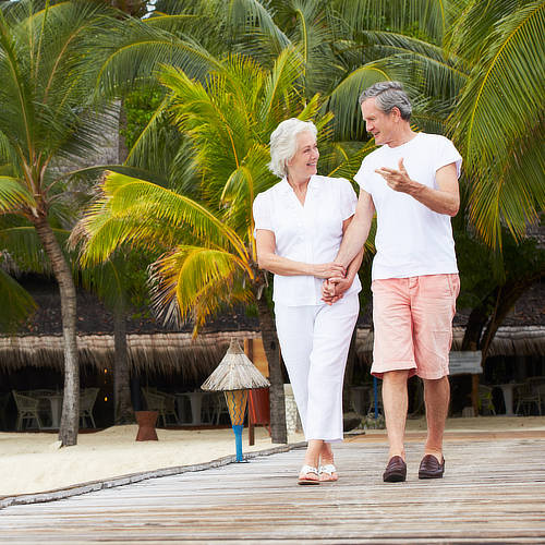 Couple enjoying retirement in the DR, walk together along beach