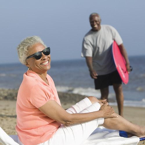 Retired couple enjoy surf, sun and sand on beach near Sosua, Puerto Plata