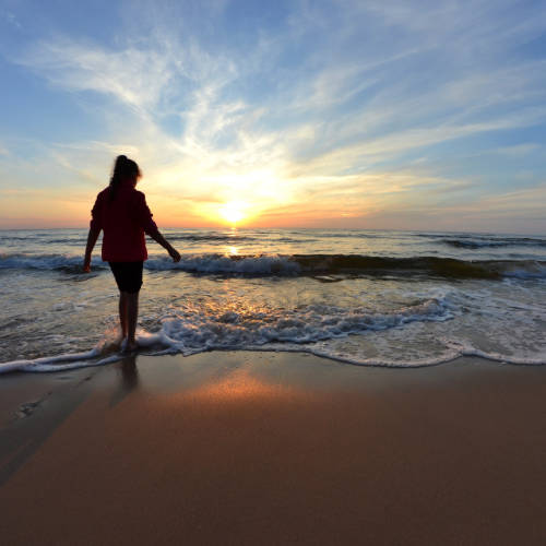 Woman walks sandy beach as sun sets over horizon